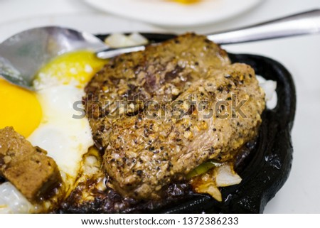 Beefsteak with egg and butter on cast iron #1372386233