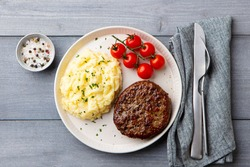 Beefsteak with mashed potato on a plate. Grey wooden background. Close up. Top view.