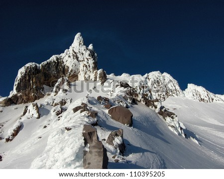 Beep blue skies above, white powdery snow covers the rocky summit of Mt. Hood in Oregon in The United States of America