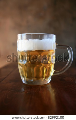 Beer. a mug of fresh poured ice cold beer in a restaurant with a pleasing dark background wall
