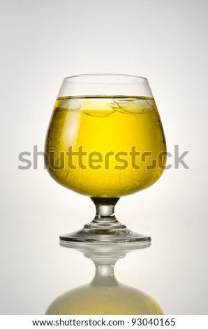 Beer and ice in glass with reflection on a white background