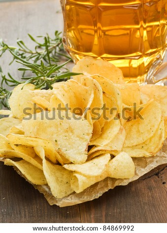 Beer and potato chips with rosemary. Shallow dof.