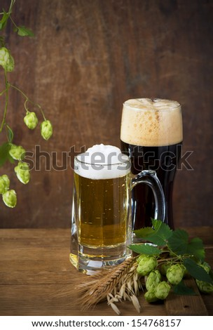 Beer barrel with beer glasses on a wooden table. The dark background