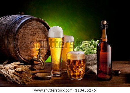 Beer barrel with beer glasses on a wooden table. The dark green background.