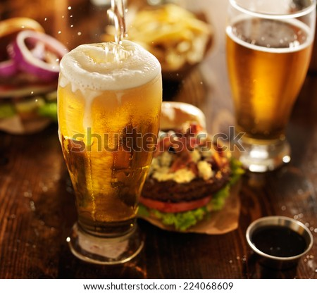beer being poured into glass with gourmet hamburgers - Shutterstock ID 224068609