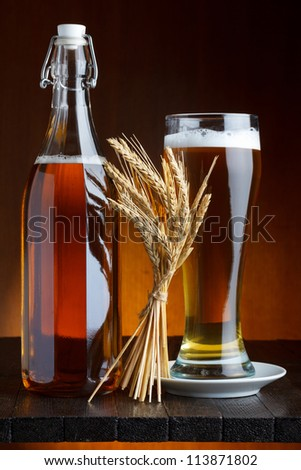Beer bottle and mug with wheat on wooden table still life