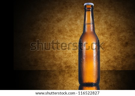 Beer bottle on yellow wooden background