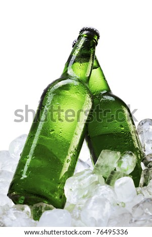 Beer bottles on ice cubes over white background