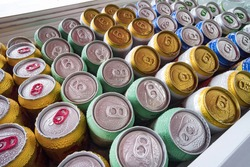 Beer cans Fresh from the fridge. Lots of aluminum cans in the ice in the open fridge. Drops of water on a cold can of drink.