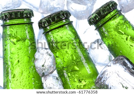 Beer chilled in ice on white-blue background