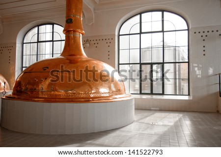 Beer factory with large storage tanks inside - stock photo