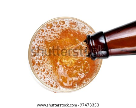 Beer flow in a glass from a brown bottle, top view
