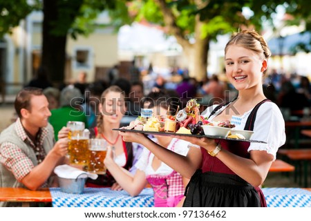 Beer garden restaurant in Bavaria, Germany - beer and snacks are served, the waitress also wears traditional costume