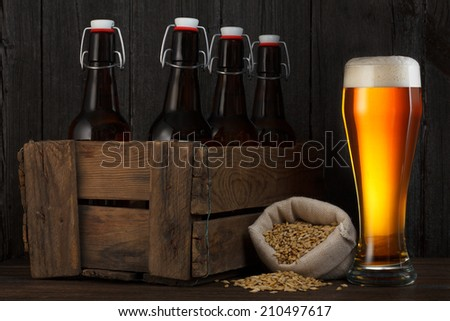 Beer glass and beer barley in bag with wooden box full of bottles on table