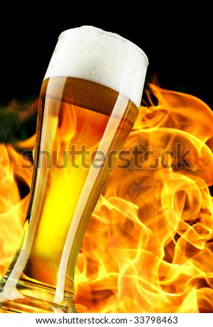 Beer glass close-up and flame in the background