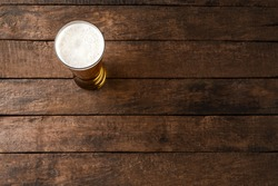 Beer glass on wooden table. Close up