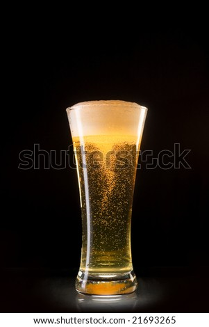 Beer glass with bubbles whirl isolated on black background