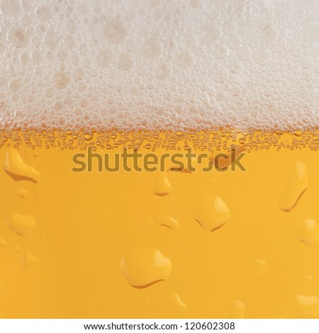 Beer in a glass with condensation and froth forming a background