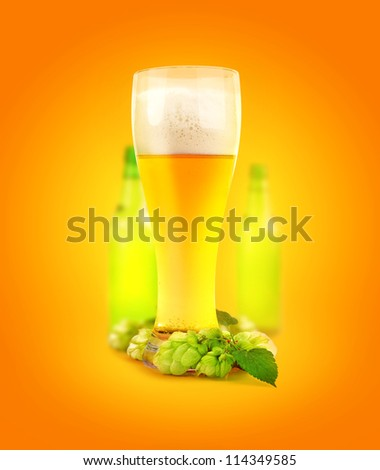 beer in glass and hop bottle of light on orange yellow abstract background