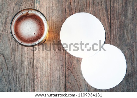 beer in glass on wooden table and blank white paper for coasters.