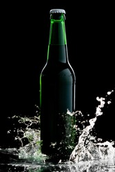 Beer in green bottle with water splash isolated on black