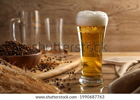 Beer in the glass and malt on wooden table background. Alcohol drink concept.