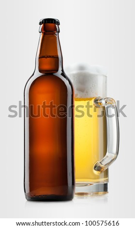 Beer into glass and bottle on a gray