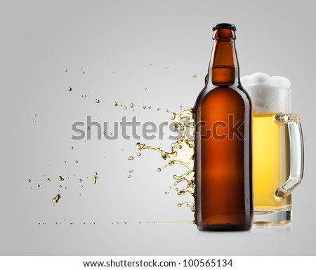 Beer into glass and bottle on a gray with splash
