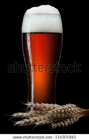 Beer into glass on a black - stock photo