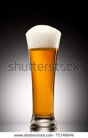 Beer into glass on a gray gradient