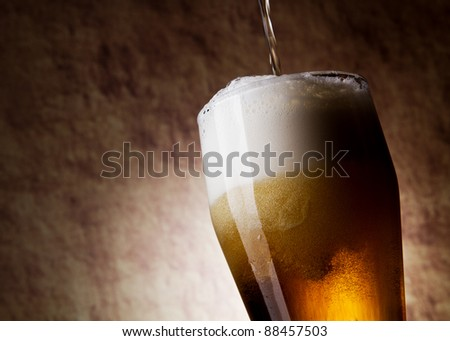 Beer into glass on a old stone