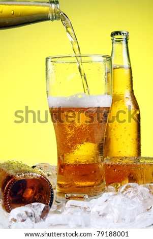 Beer is pouring into glass over yellow background