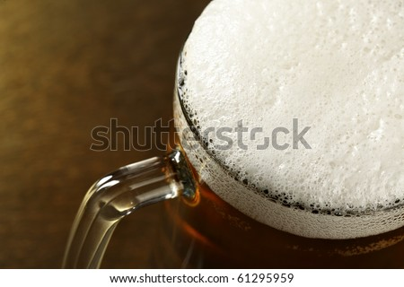 Beer mug with froth over dark background