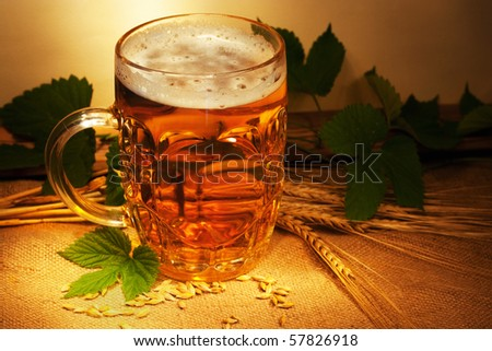 beer on sacking with wheat and hop in ambient light still-life
