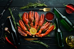 Beer party. Beer, snacks and lobster claws on a black background. Rustic style. Seafood delicacies.