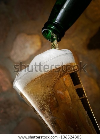 Beer pouring in a glass on stone wall