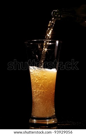 Beer pouring into glass on a black background - stock photo