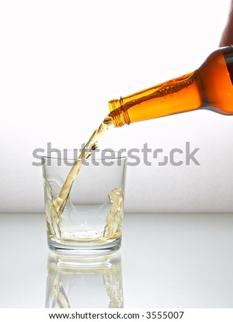 Beer pouring into glass on a white reflect background