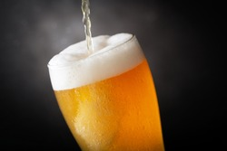 beer pouring into glass on dark background