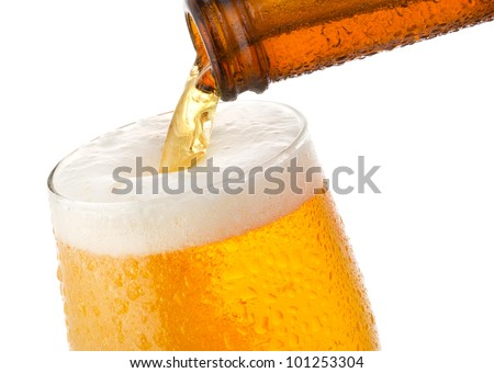 Beer pouring into glass on white background