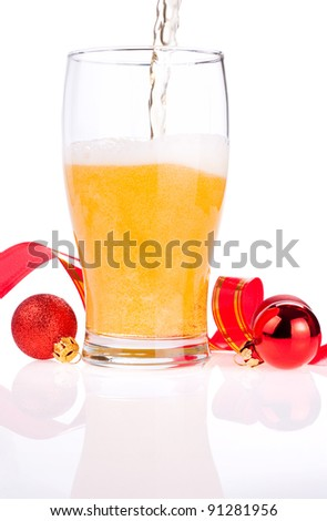 Beer pouring into glass, Red ribbon and Christmas Balls isolated on white background