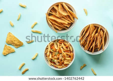 Beer snack, nachos chips, peanuts and cheese sticks in white bowls on a blue background. Top view, copy space, minimalistic.