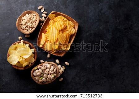 Beer snacks on stone table. Various nuts, potato chips. Top view with copy space