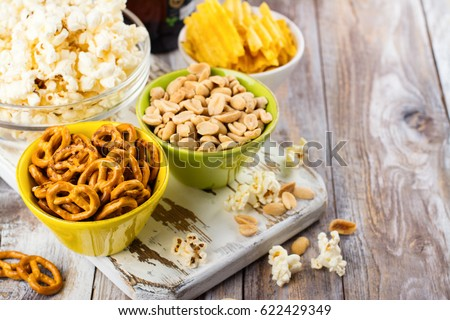 Beer snacks on wooden table - nuts, chips and popcorn in bowls ready for eating. Football fan party. Copy space