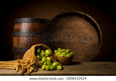 Beer. Still life with Vintage beer barrel and glass light beer. Fresh amber beer concept. Green hop and gold barley on wooden table. Ingredients for brewery. Brewing traditions ストックフォト ©