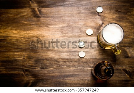 Beer style- bottle, beer in the glass and covers on wooden table. Free space for text. Top view