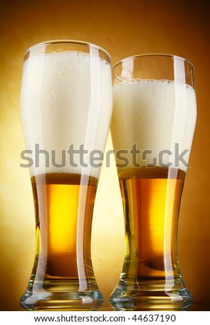 Beer with froth close-up over yellow background - stock photo