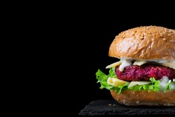 Beet burger with lettuce, cheese and yogurt sauce against the black background. Healthy no meat alternative. Low key photo. Copy space