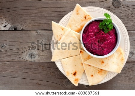 Beet hummus dip with pita bread on a plate, above view on a rustic wooden background