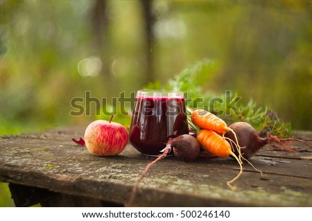 beet  juice in glass on wooden table